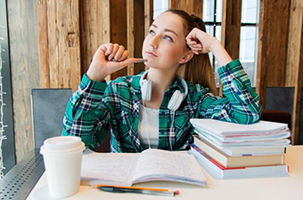 Student at desk piled with papers, thinking